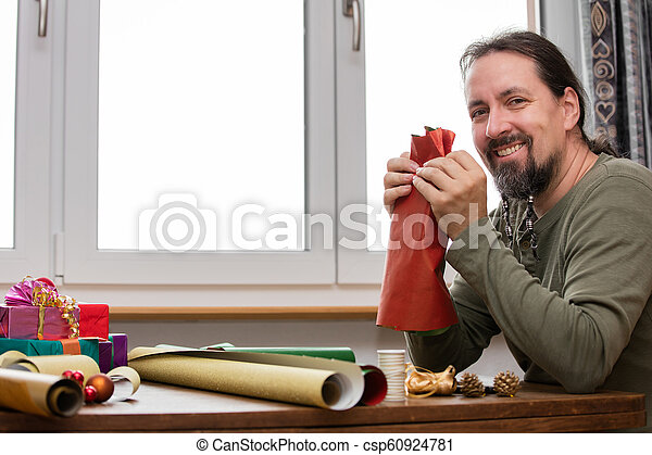 man is wrapping colorful gifts - csp60924781