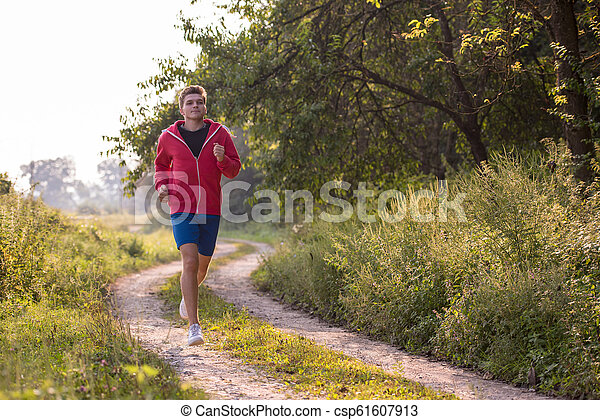 man jogging along a country road - csp61607913