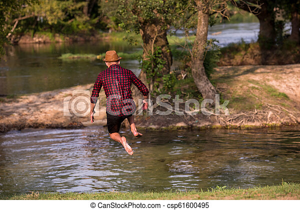 man jumping into the river - csp61600495