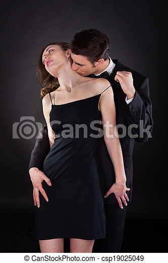 Man Kissing Woman On Neck While Removing Dress Strap - csp19025049
