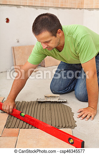 Man Laying Ceramic Floor Tiles Checking Lines With A Level