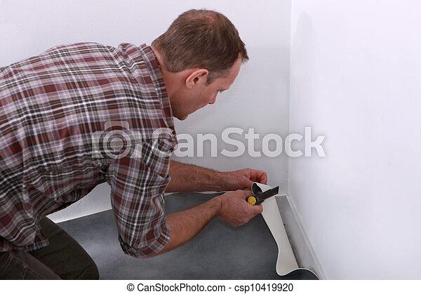 Man laying down linoleum flooring - csp10419920