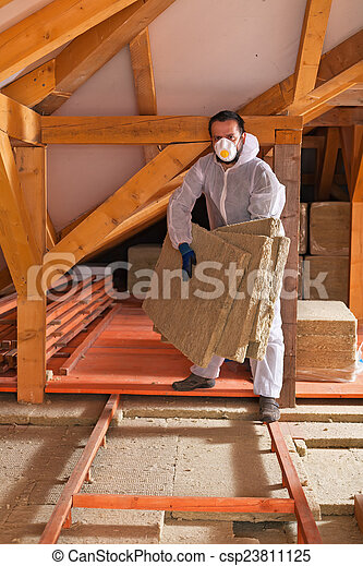 Man laying thermal insulation layer under the roof - csp23811125