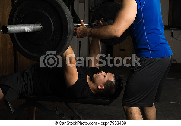 Man Lifting Weights With A Trainer   Csp47953489