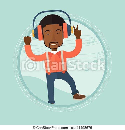 Man listening to music in headphones and dancing. - csp41498676
