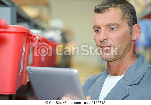 man looking at the tablet - csp42120712