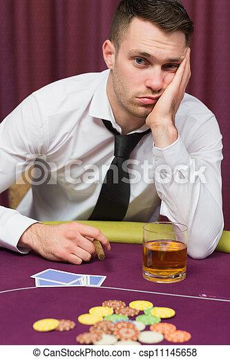 Man looking depressed at poker table - csp11145658