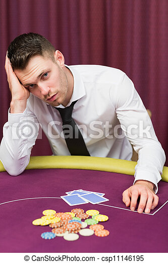 Man looking unhappy at poker table - csp11146195