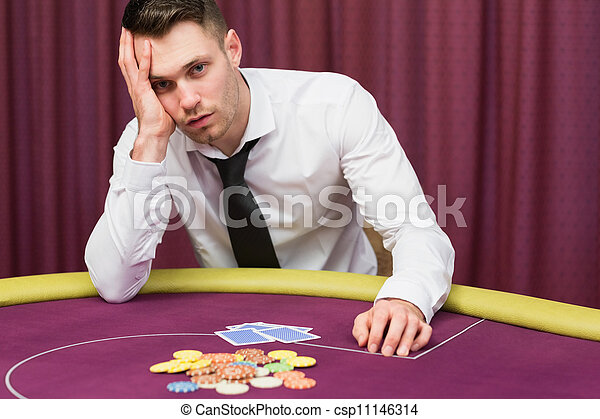 Man looking worried at poker table - csp11146314