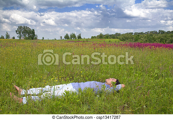 Man lying on a spring meadow - csp13417287