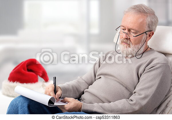 man making the shopping list for holidays next to a red hat csp53311863