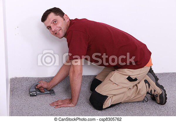 man on all fours stapling carpet - csp8305762