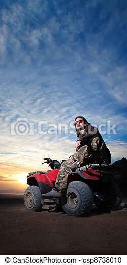 man on atv on the desert sunrise background - csp8738010