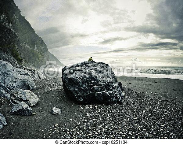 man on rock watching the sea - csp10251134