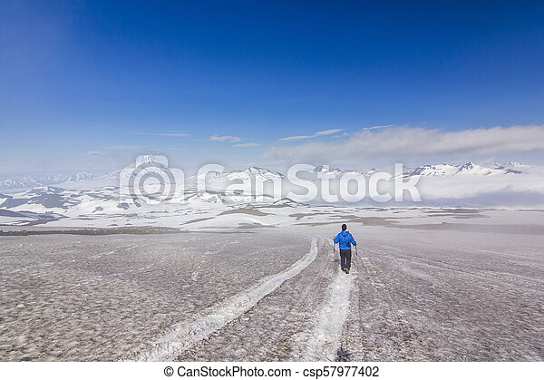 man on snowy field in kamchatka mountains near covered by snow volcanoes - csp57977402
