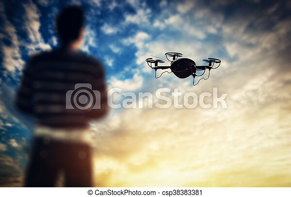 Man operating a drone at sunset. - csp38383381