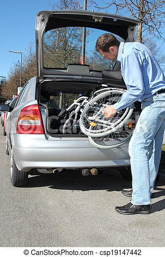 Man packing a wheelchair in a car's trunk - csp19147442