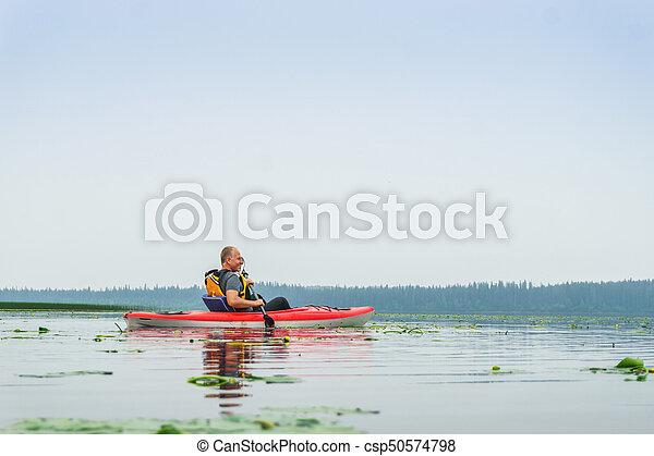 Man paddling kayak among lily flowers on the lake - csp50574798