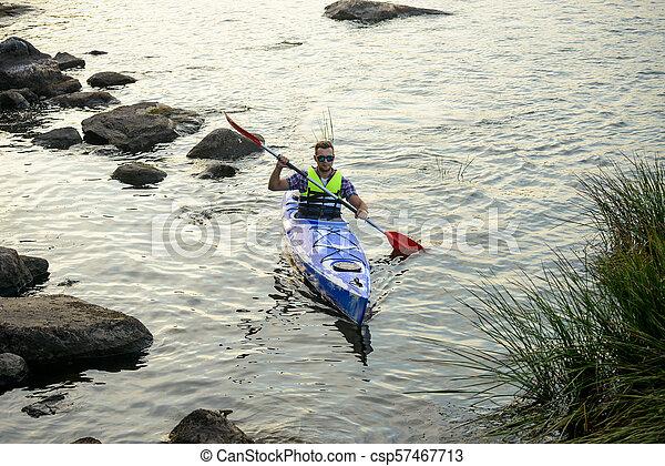 Man Paddling Kayak on Beautiful River or Lake among Stones at the Evening - csp57467713