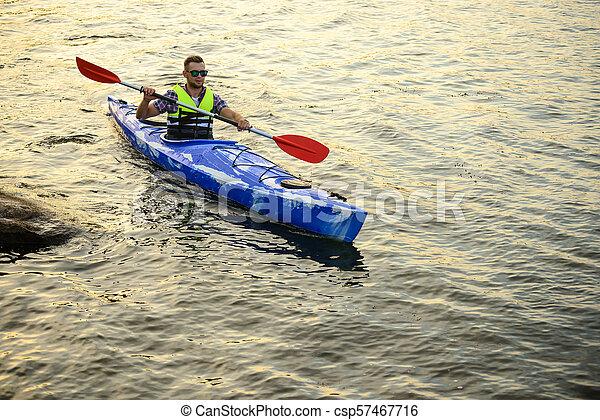 Man Paddling Kayak on Beautiful River or Lake among Stones at the Evening - csp57467716