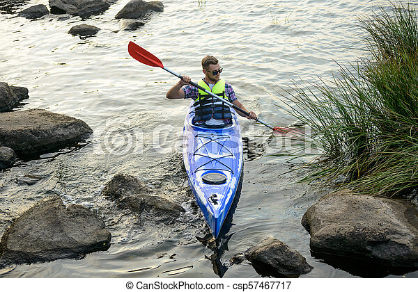 Man Paddling Kayak on Beautiful River or Lake among Stones at the Evening - csp57467717