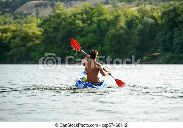 Man Paddling Kayak on Beautiful River or Lake at the Evening - csp57468112