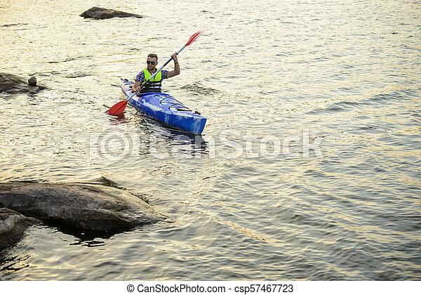 Man Paddling Kayak on Beautiful River or Lake among Stones at the Evening - csp57467723