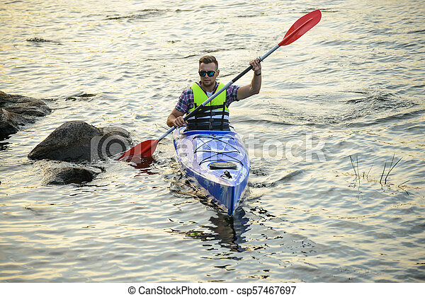 Man Paddling Kayak on Beautiful River or Lake among Stones at the Evening - csp57467697