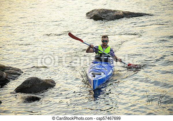 Man Paddling Kayak on Beautiful River or Lake among Stones at the Evening - csp57467699