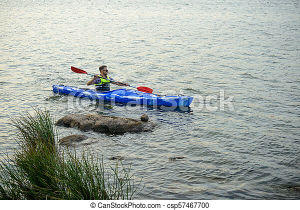 Man Paddling Kayak on Beautiful River or Lake among Stones at the Evening - csp57467700