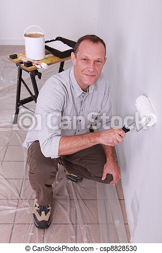 Man painting a wall white - csp8828530