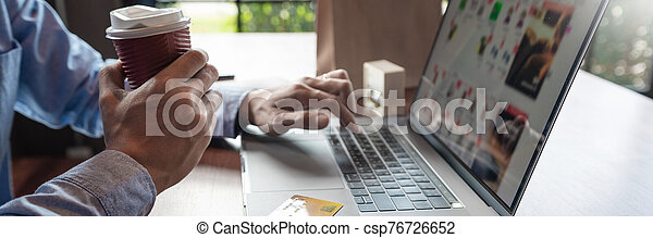 Man paying with credit card and entering security code for online shopping making a payment or purchasing goods on the internet with laptop computer, online shopping concept - csp76726652