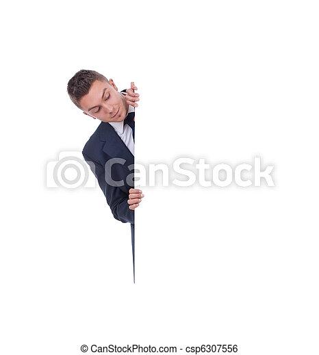 man peeking behind white billboard - csp6307556