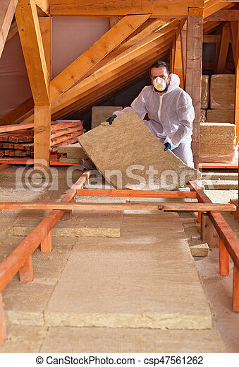 Man places rockwool thermal insulation between wooden scaffolding - csp47561262