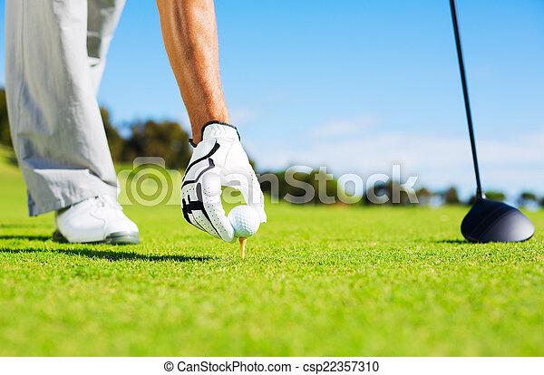 Man Placing Golf Ball on Tee - csp22357310