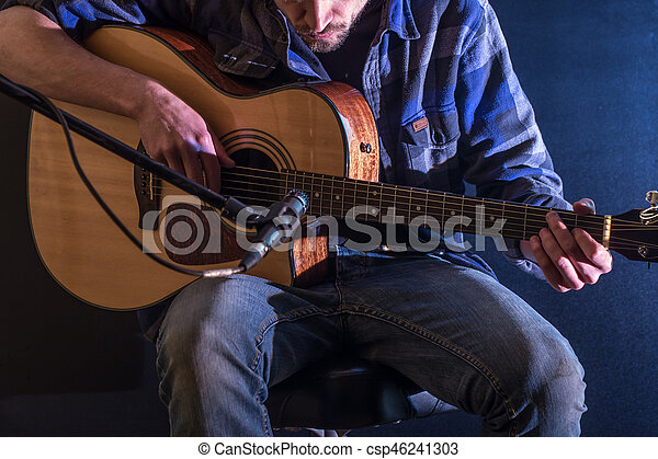 Man Playing Acoustic Guitar On A Black Background The Music Concept
