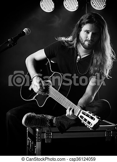 Man Playing Acoustic Guitar On Stage Photo Of A Young Man With Long