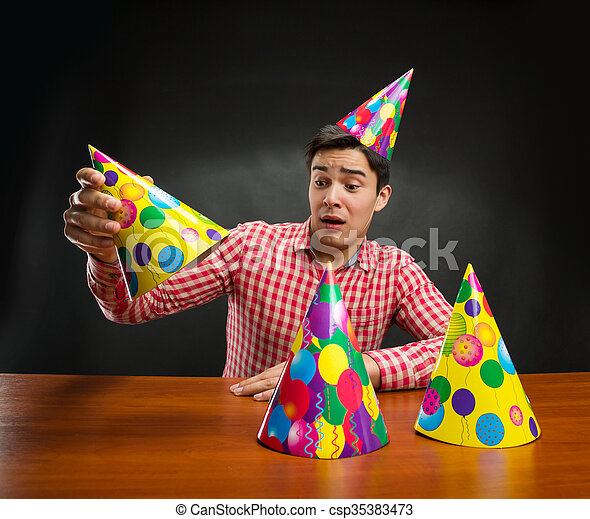 Young man playing with Birthday hats at the table
