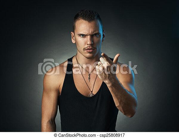 man points a finger on black background - csp25808917
