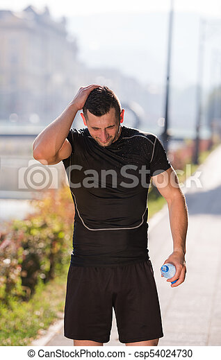 man pouring water from bottle on his head - csp54024730