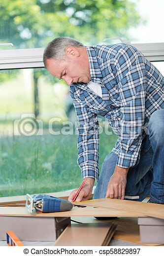 Man preparing laminate floorboard - csp58829897
