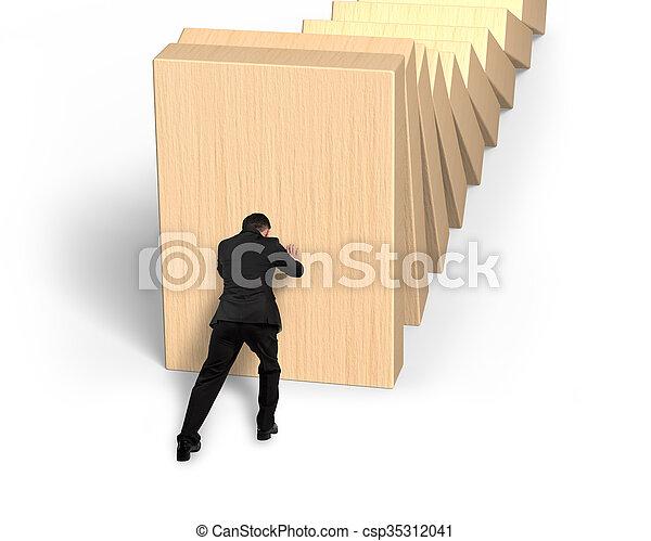 Man pushing and stopping dominoes falling - csp35312041