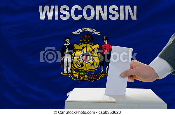 man putting ballot in a box during elections  in front of flag american state of wisconsin - csp8353620