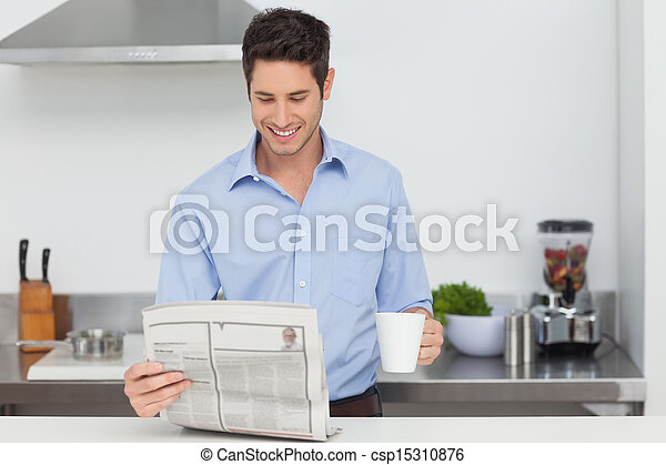 Man reading a newspaper in the kitchen - csp15310876