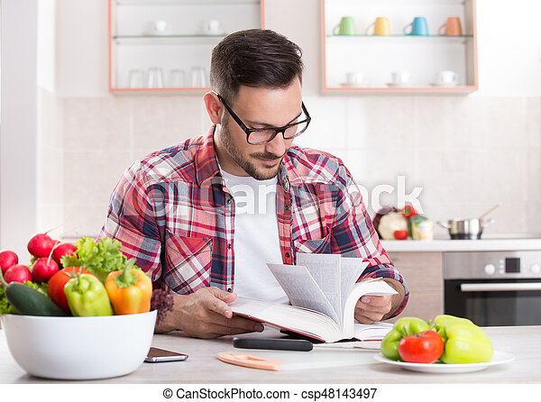 Man reading recipe book in kitchen smiling handsome man sitting at man reading recipe book in kitchen csp48143497 forumfinder Image collections