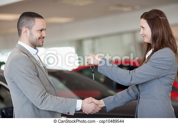 Man receiving car keys while shaking hand - csp10489544
