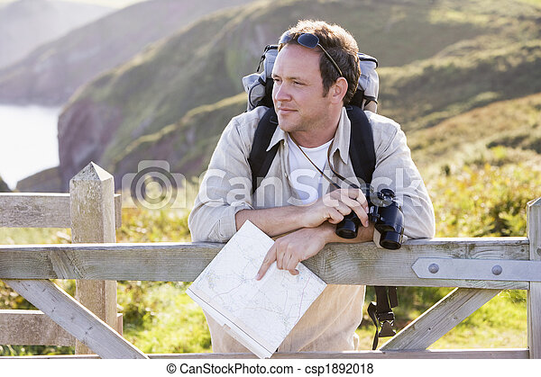 Man relaxing on cliffside path holding map and binoculars - csp1892018