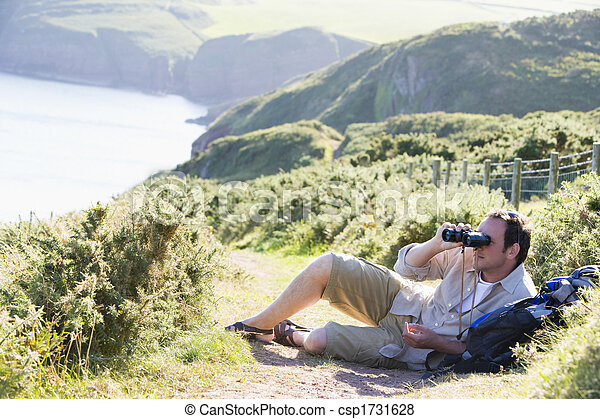 Man relaxing on cliffside path using binoculars - csp1731628