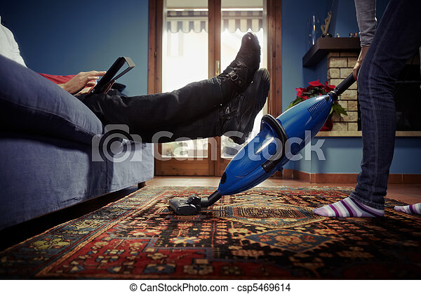 man relaxing while woman doing chores at home - csp5469614