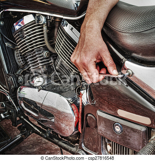 man repairing a classic motorcycle in hdr - csp27816548